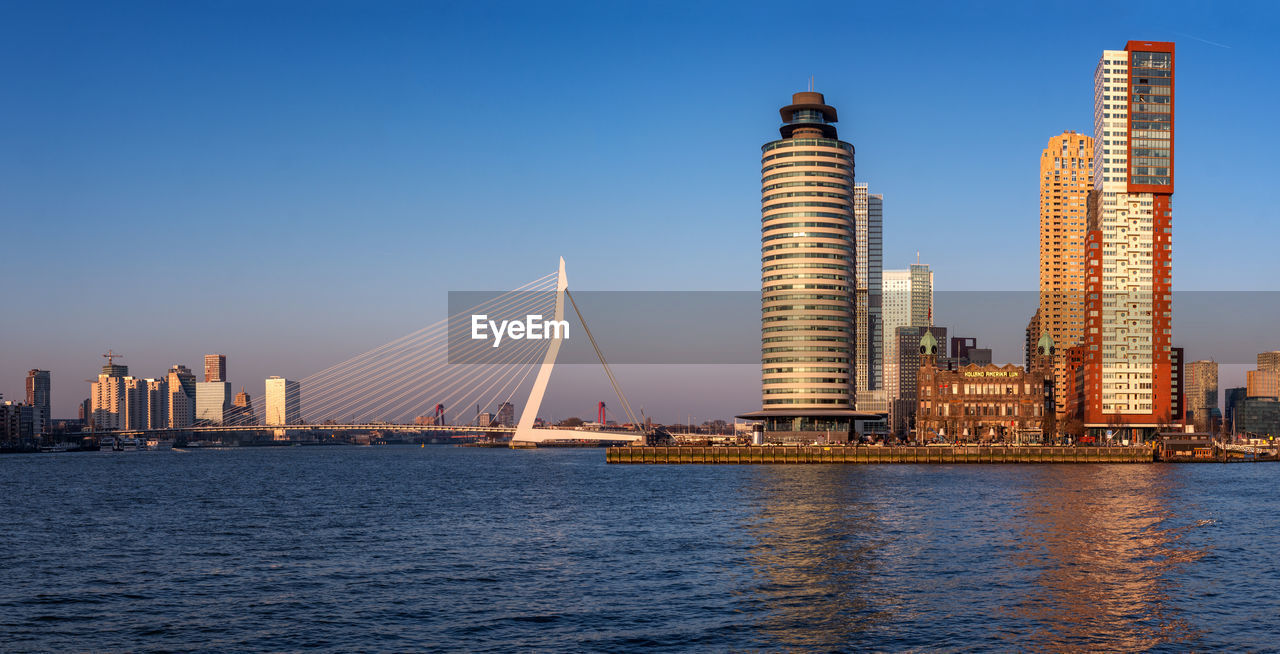 built structure, water, architecture, sky, building exterior, waterfront, city, office building exterior, skyscraper, clear sky, building, tall - high, nature, sea, modern, urban skyline, blue, transportation, no people, cityscape, outdoors, bay