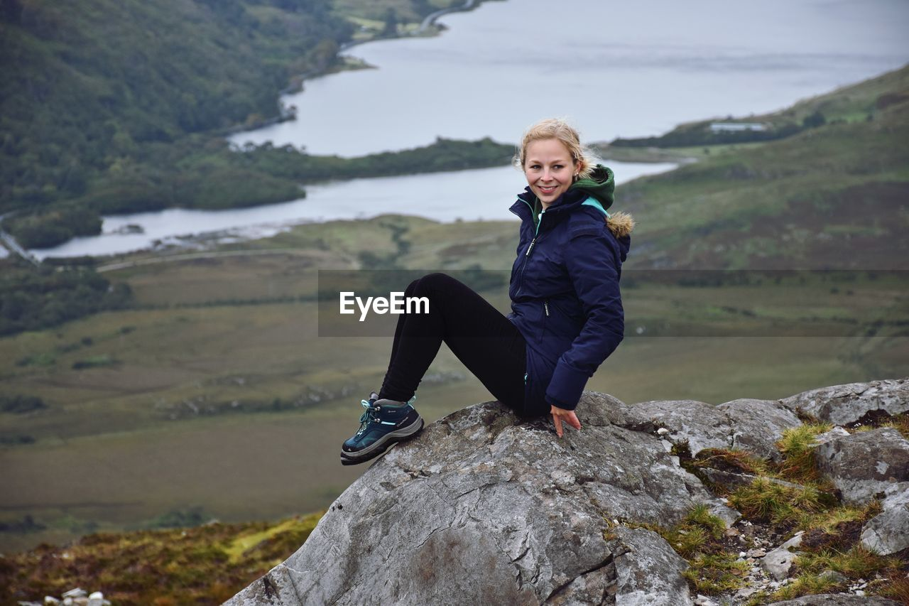 one person, real people, lifestyles, rock, full length, solid, leisure activity, rock - object, mountain, young adult, smiling, young women, women, looking at camera, nature, day, beauty in nature, portrait, outdoors