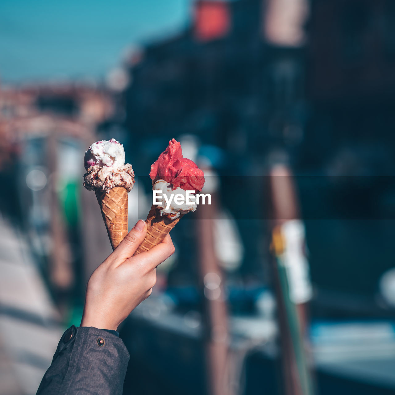 Cropped hand holding ice cream cone in city