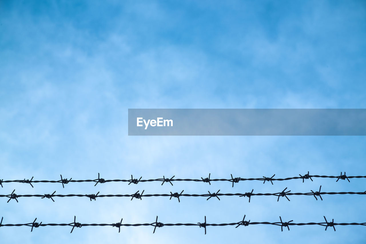 low angle view, fence, sky, protection, boundary, barrier, safety, security, no people, day, blue, metal, barbed wire, outdoors, nature, cloud - sky, wire, copy space, communication, architecture