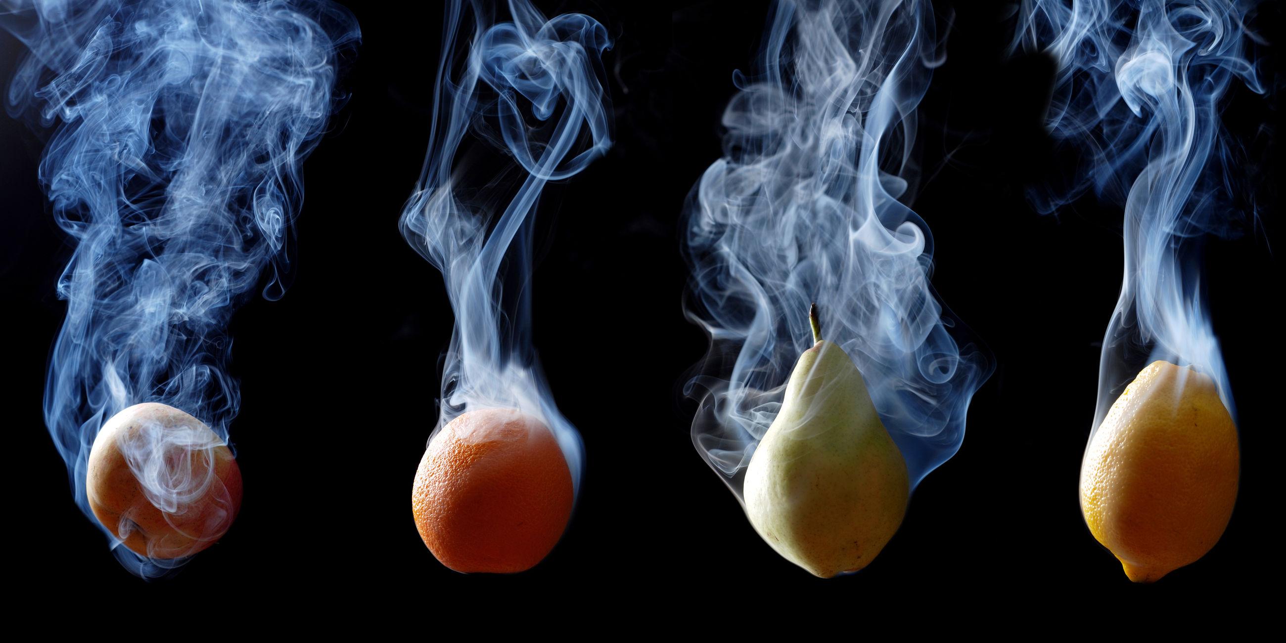 Fruits smoking against black background