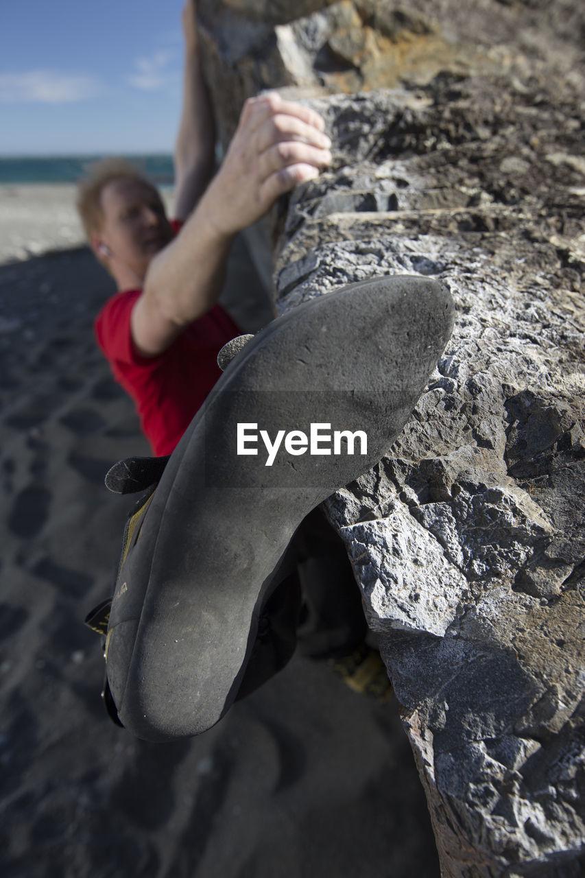 Man climbing rock at beach