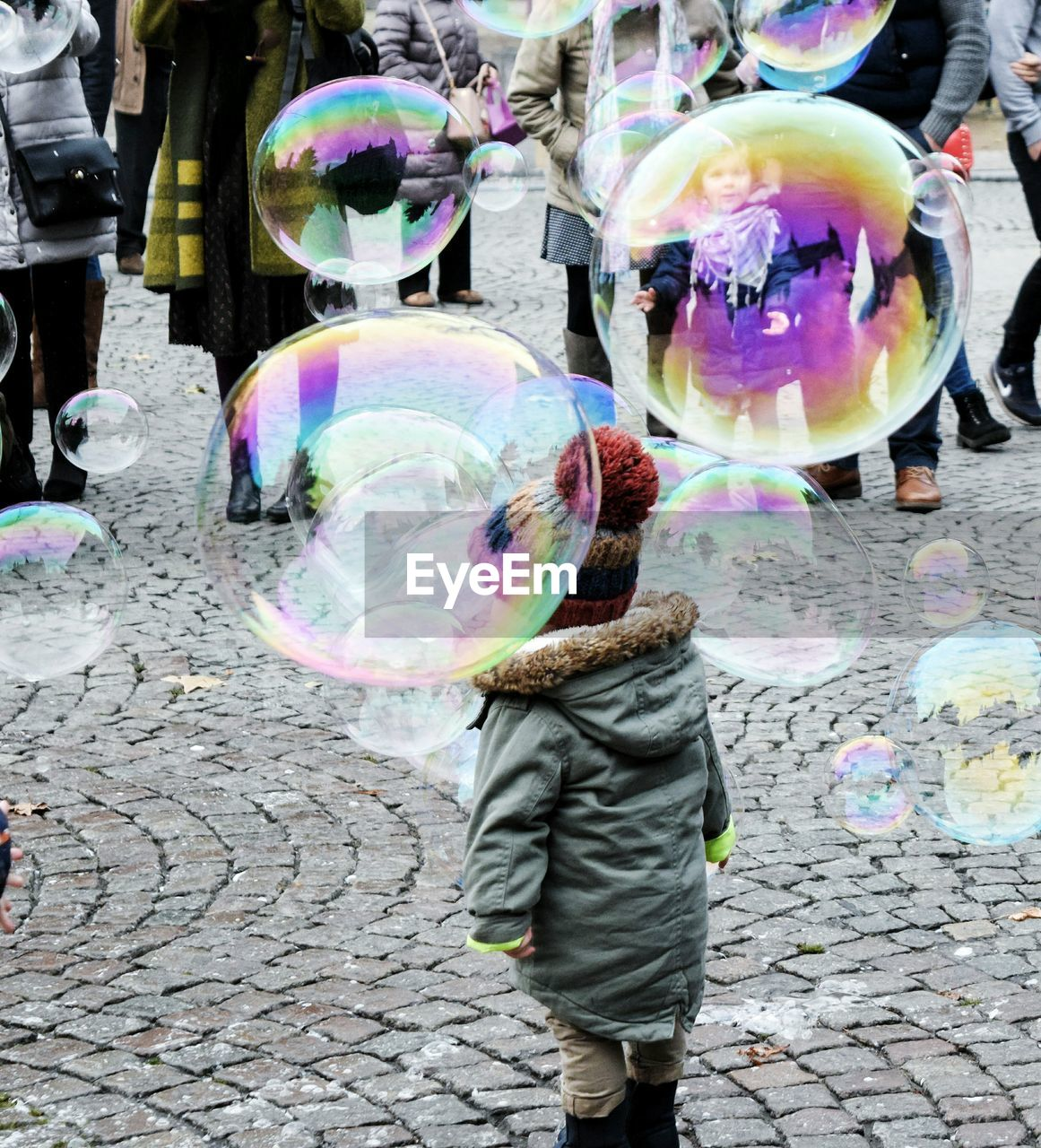 Rear View Of Boy Playing With Bubbles At Paving Stones