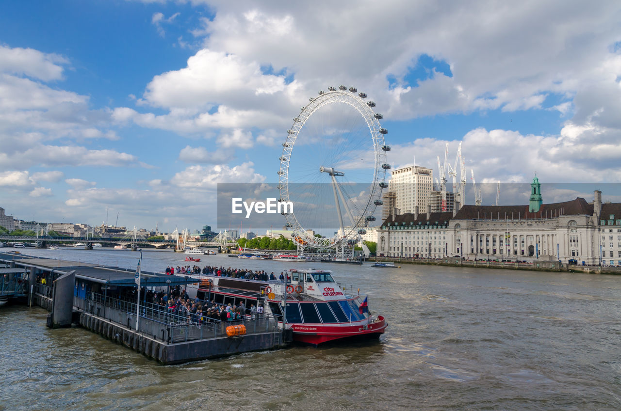 cloud - sky, nautical vessel, architecture, river, transportation, day, water, sky, built structure, ferris wheel, building exterior, waterfront, mode of transport, outdoors, travel destinations, no people, harbor, city