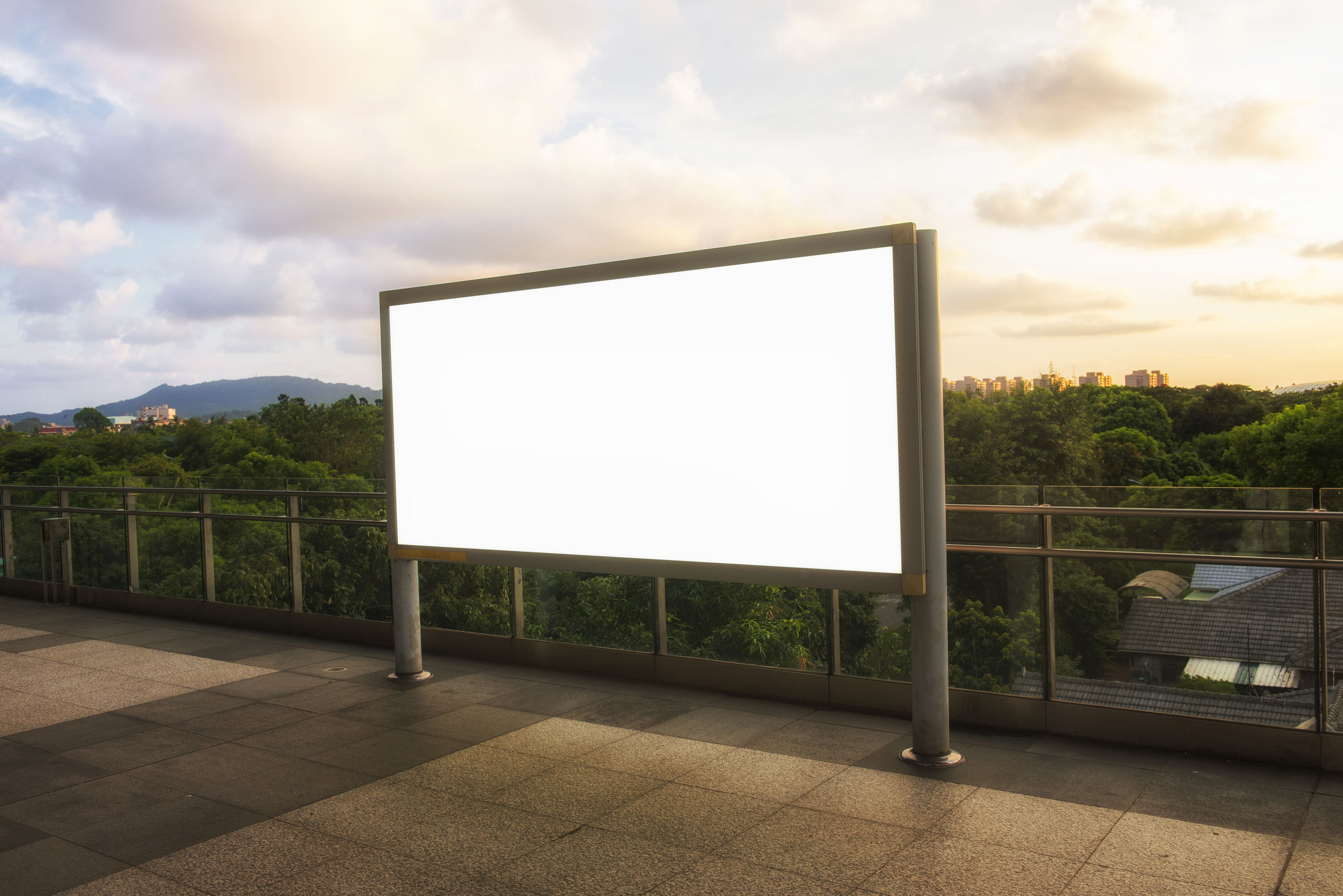 Blank billboard on footpath against cloudy sky during sunset