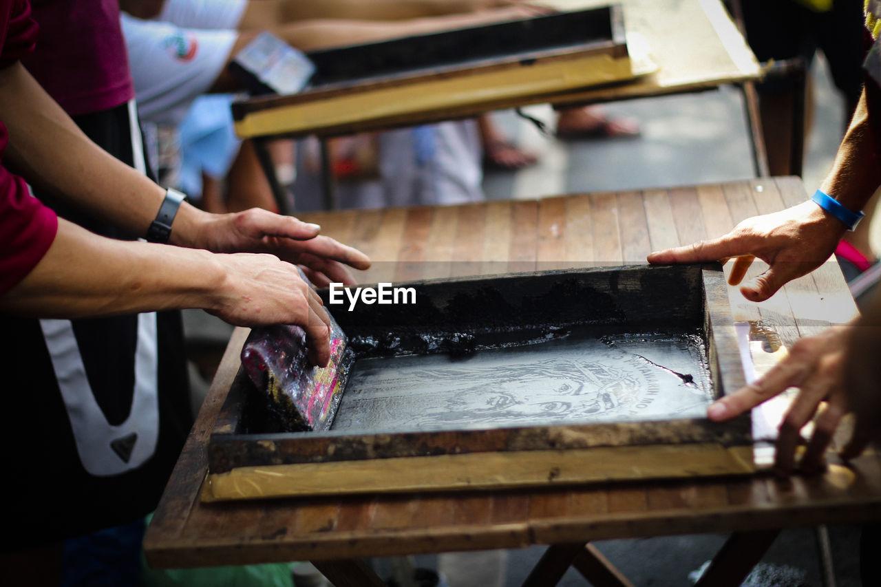 Cropped Image Of People Screen Printing At Workshop