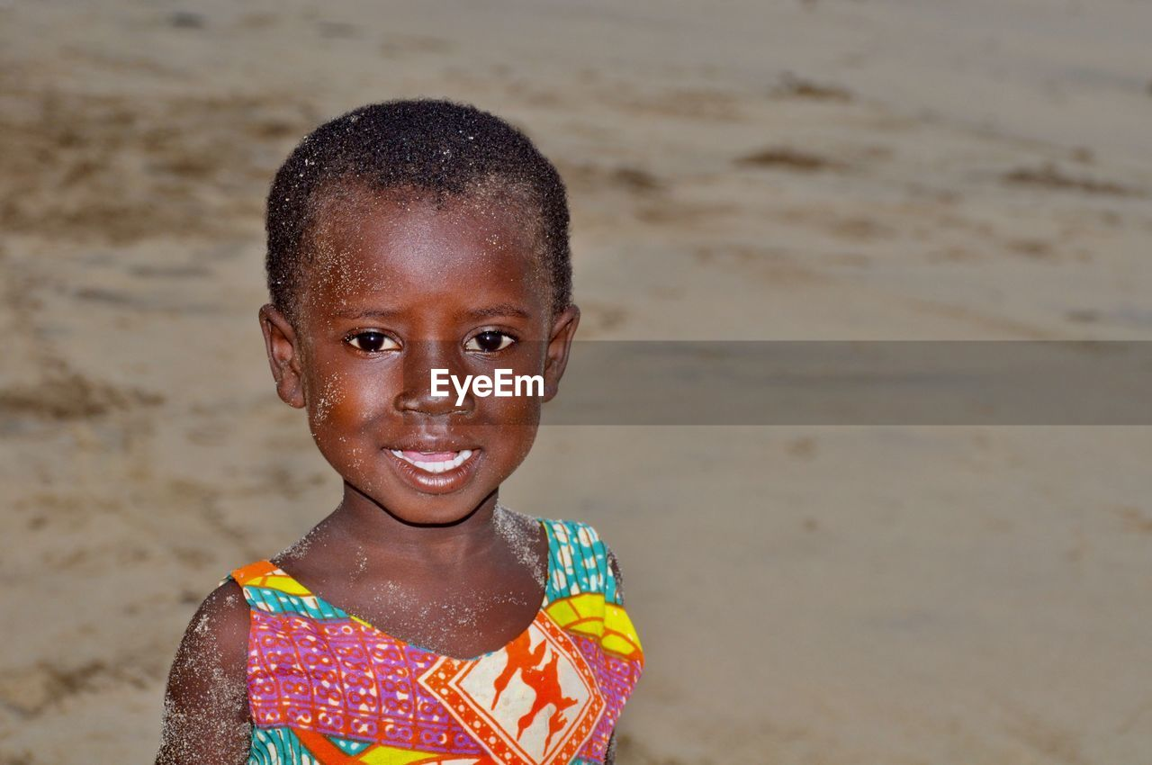 Portrait of smiling girl with sands on body standing at beach