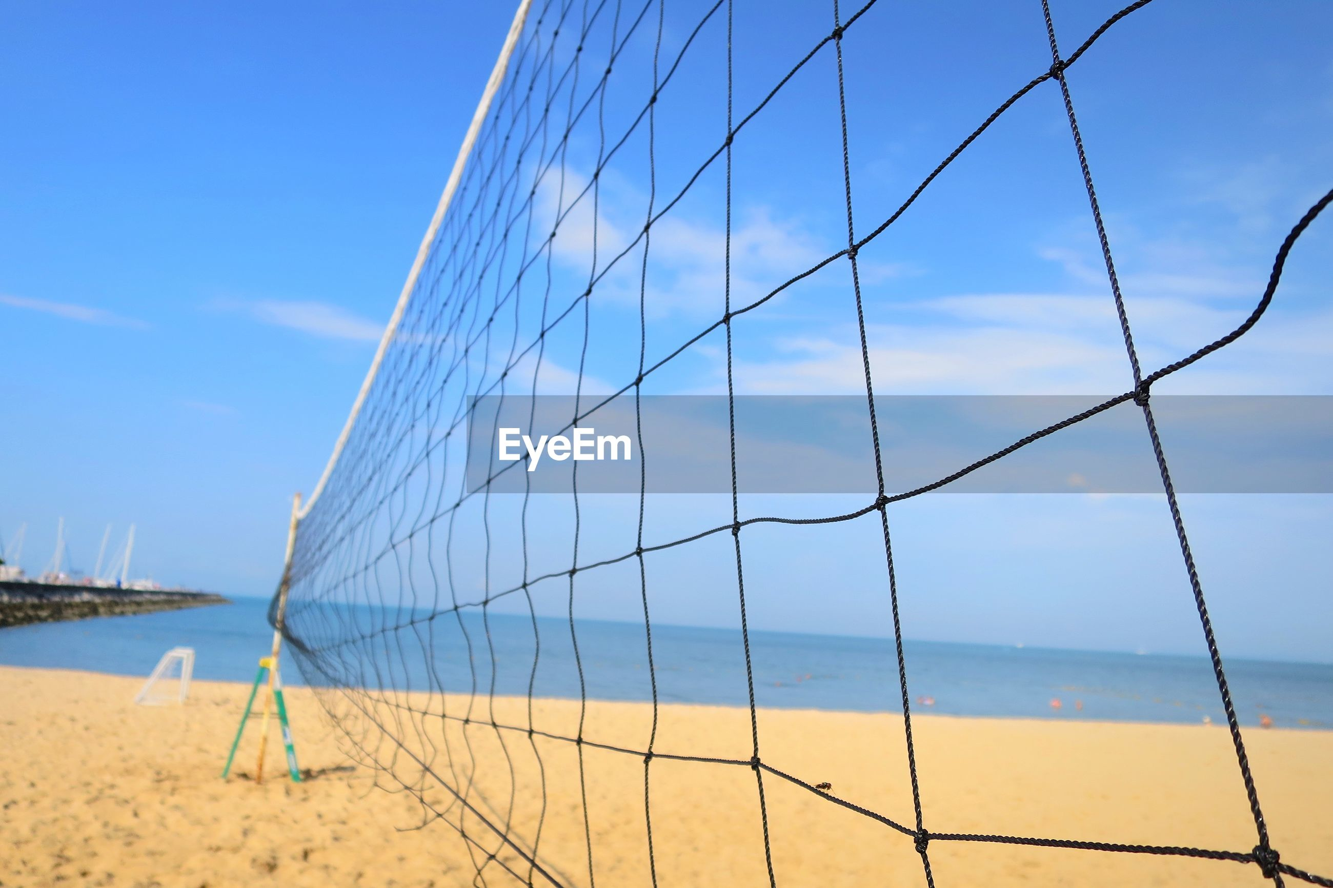 Close up of volleyball net with sea beach and blue sky in summer.