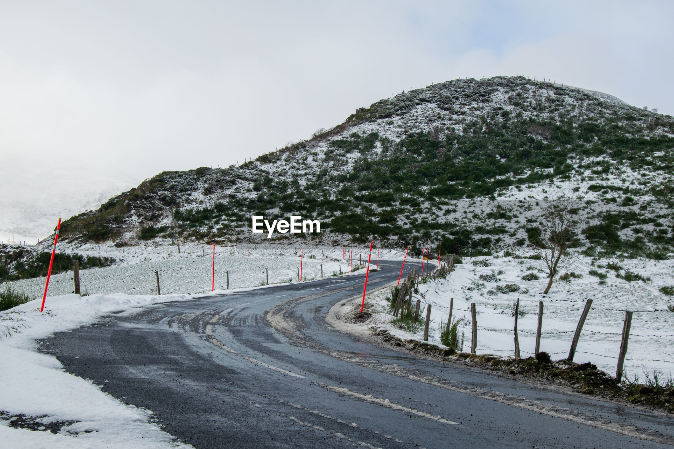 Road by mountain against sky during winter