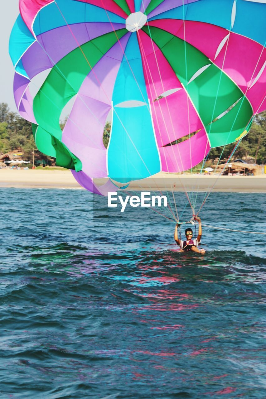leisure activity, water, real people, one person, lifestyles, sea, adventure, men, waterfront, weekend activities, outdoors, day, nature, enjoyment, fun, multi colored, parachute, extreme sports, women, beauty in nature, sky, people