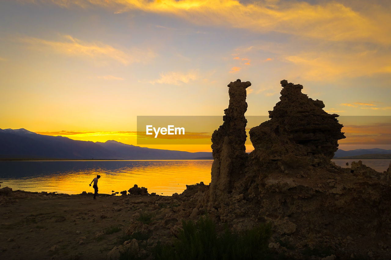sky, sunset, beauty in nature, scenics - nature, tranquility, orange color, nature, rock, water, tranquil scene, land, silhouette, beach, idyllic, rock - object, sea, cloud - sky, non-urban scene, mountain, outdoors