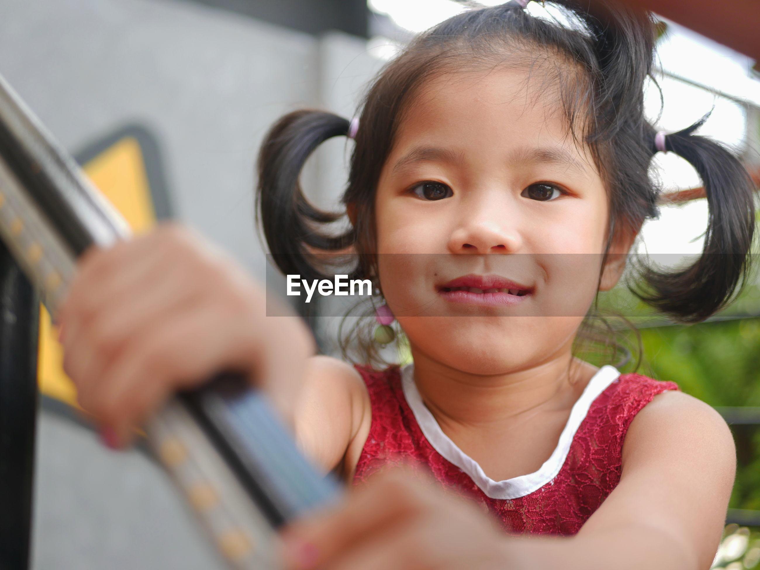 Portrait of cute girl by railing