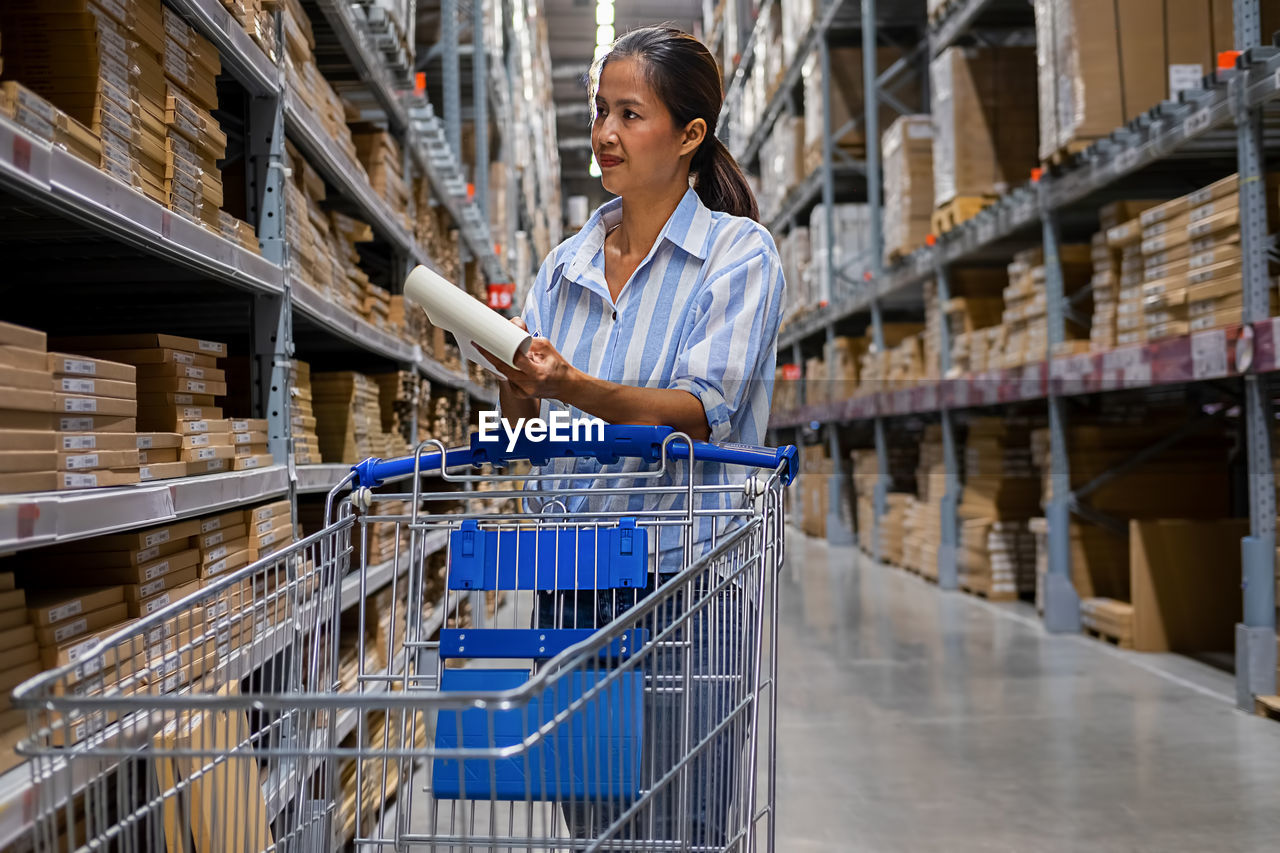 Smiling Mid Adult Woman With Checklist Working In Warehouse