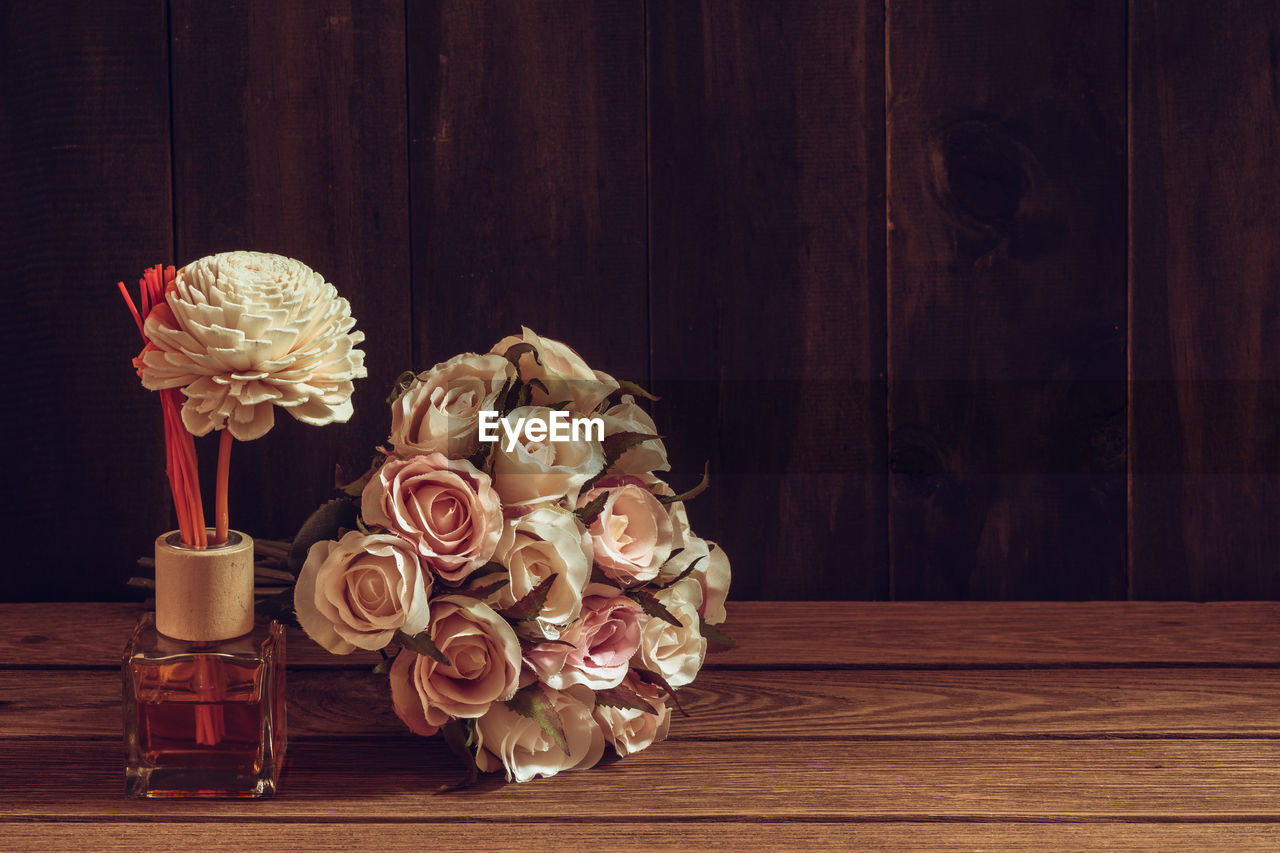flower, wood - material, table, flowering plant, plant, indoors, rose, vase, beauty in nature, freshness, rose - flower, still life, no people, close-up, vulnerability, petal, fragility, nature, container, flower head, flower arrangement, bouquet, antique, luxury, bunch of flowers