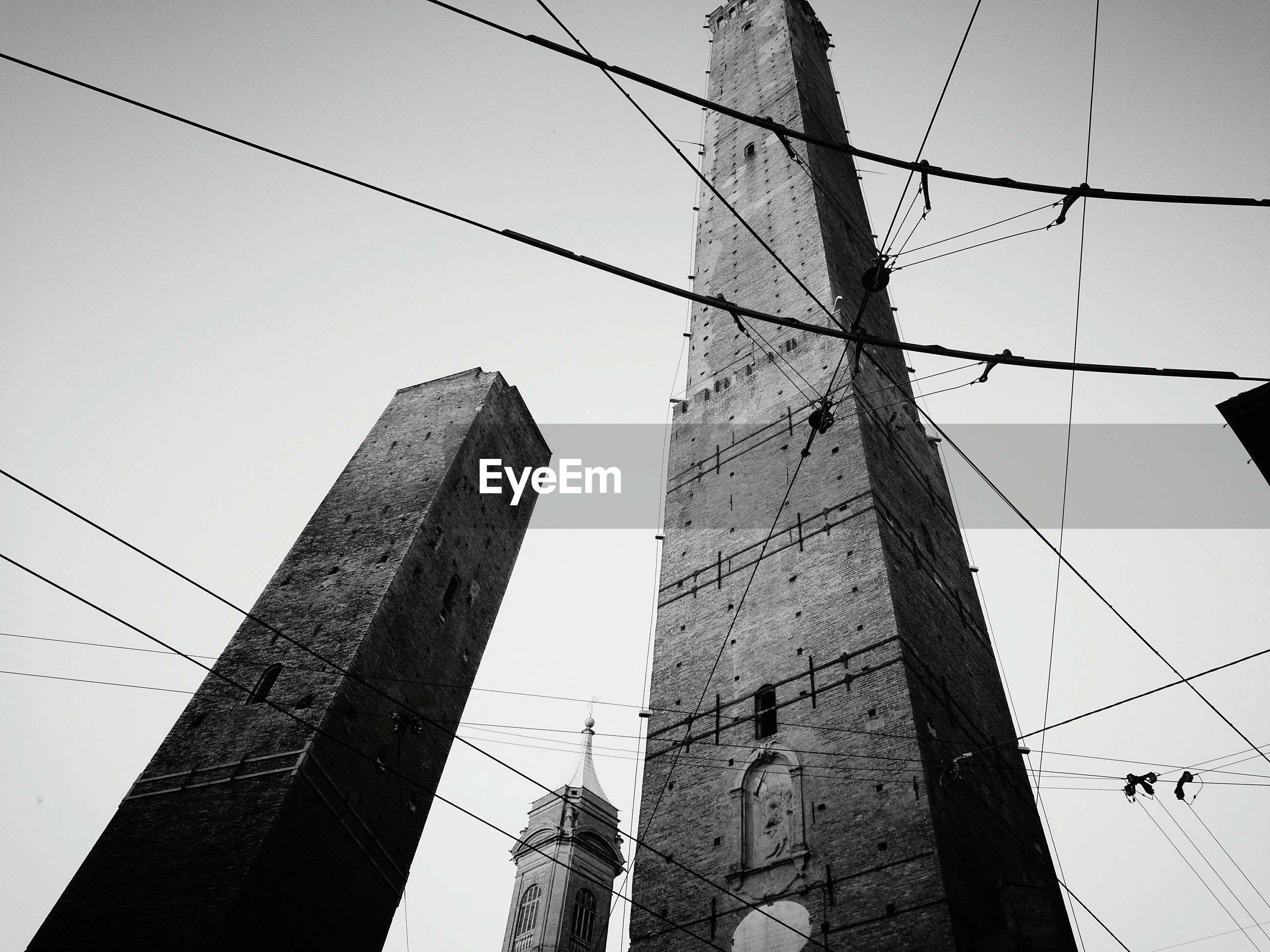 cable, low angle view, connection, power line, power supply, architecture, built structure, outdoors, day, fuel and power generation, electricity, sky, building exterior, no people, electricity pylon, technology, clear sky, telephone line