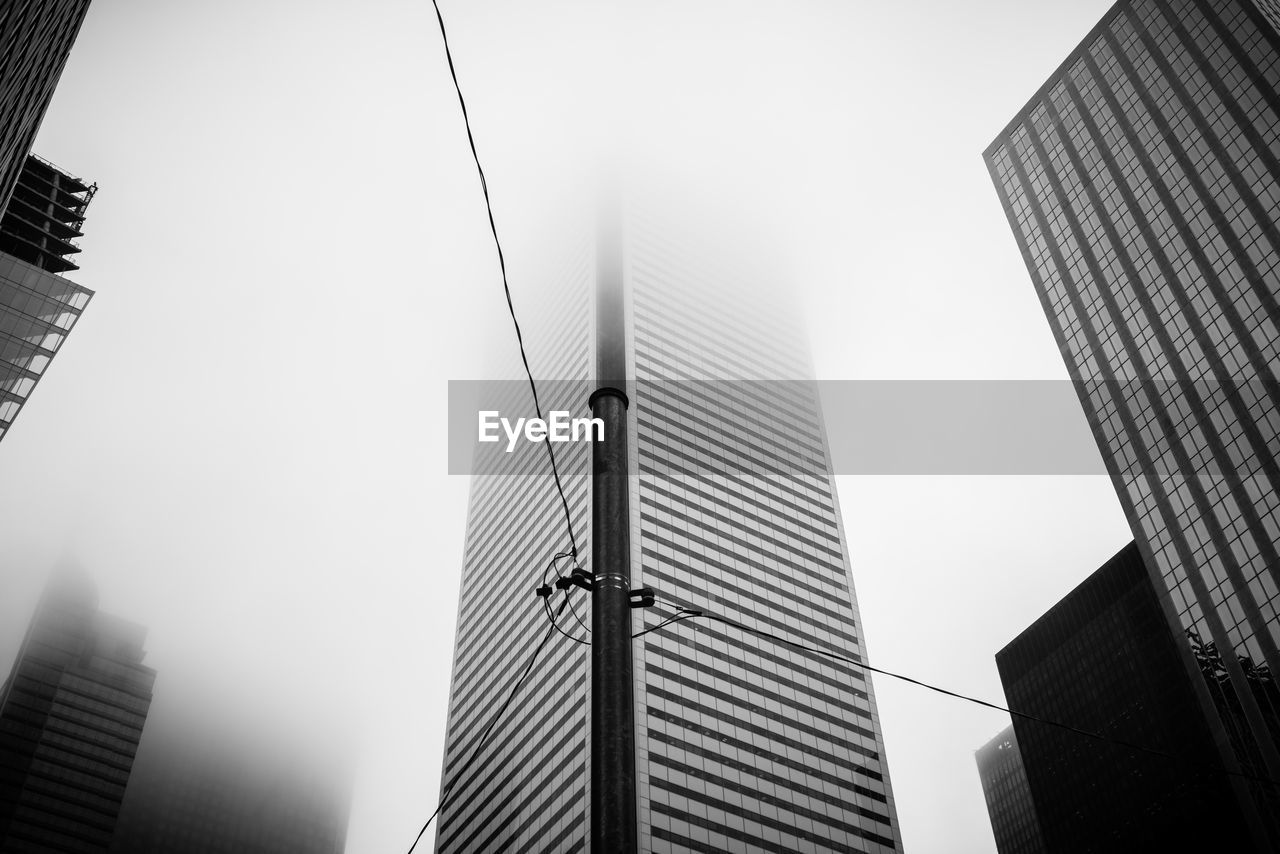 Low Angle View Of Skyscrapers Disappearing Into Fog