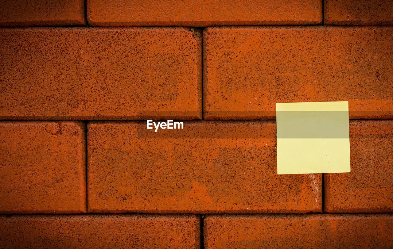 Blank yellow note on brick wall