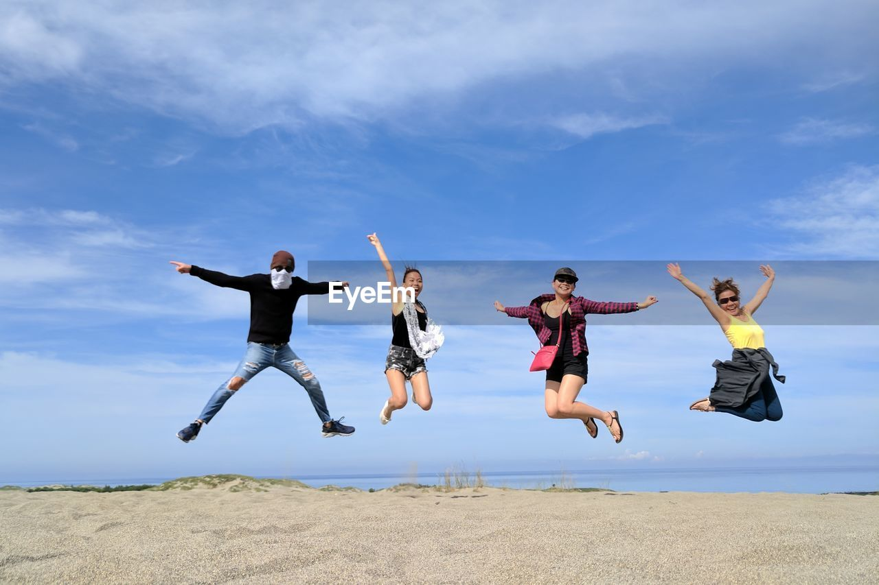 Happy friends jumping at beach against blue sky
