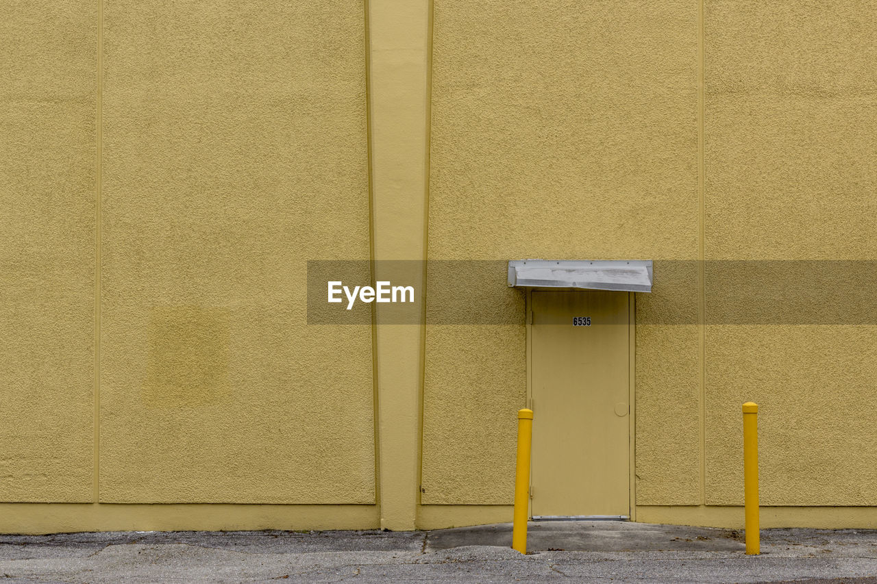 yellow, wall - building feature, built structure, architecture, building exterior, no people, day, security, safety, outdoors, wall, protection, building, door, entrance, pipe - tube, communication, mail, mailbox, pole
