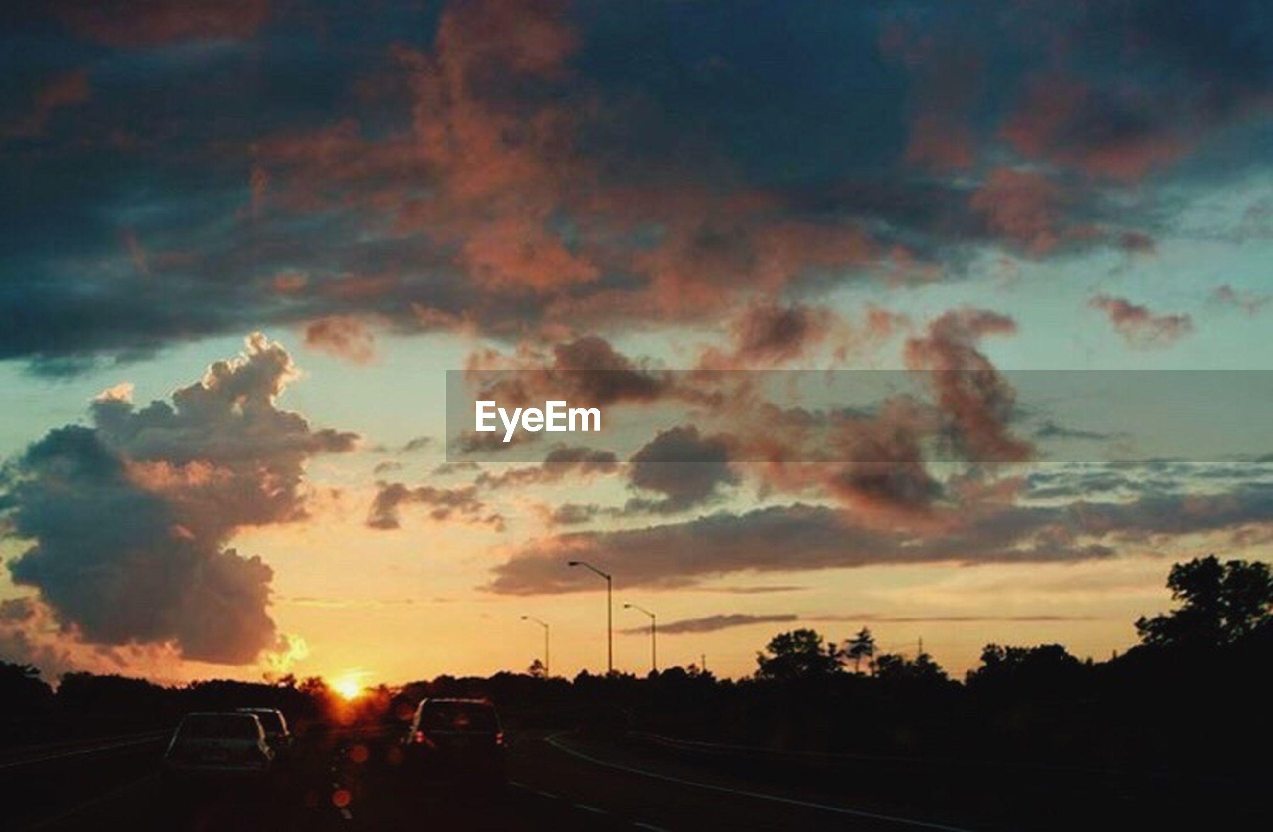 sunset, transportation, car, land vehicle, sky, road, mode of transport, cloud - sky, sun, silhouette, orange color, street, sunlight, tree, the way forward, sunbeam, beauty in nature, cloudy, nature, scenics