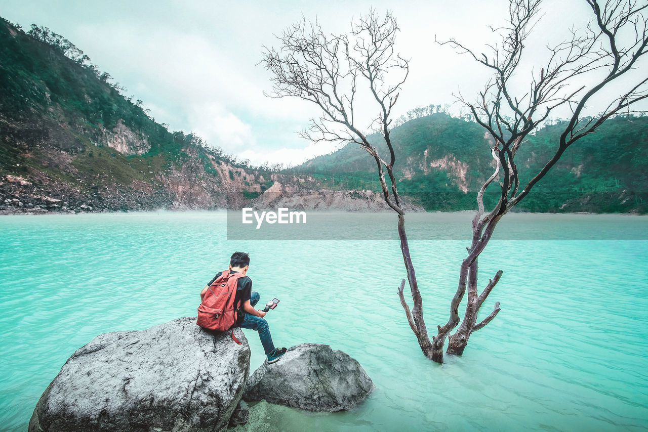 Rear View Of Man Sitting On Rocks In Lake Against Mountains