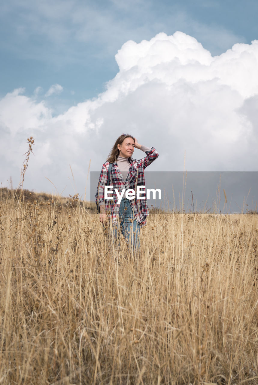 Woman looking away while standing on field against cloudy sky