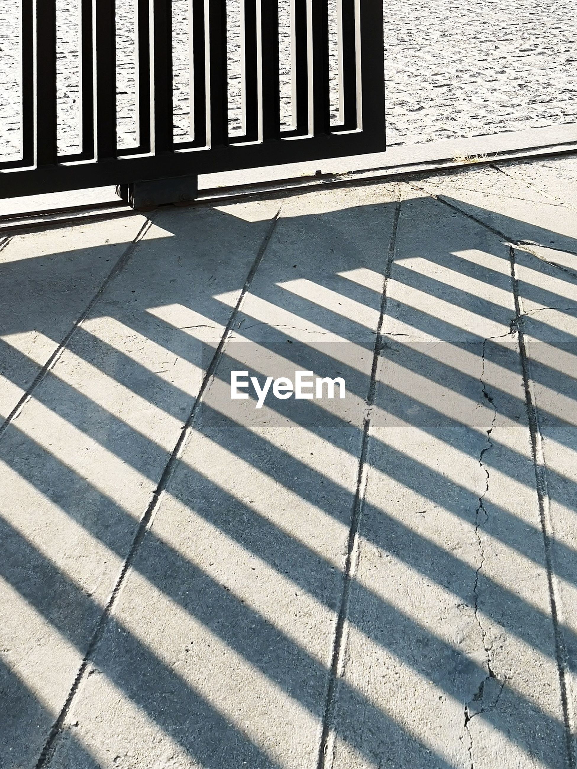 shadow, sunlight, day, nature, no people, architecture, pattern, outdoors, street, flooring, footpath, city, built structure, railing, striped, security, absence, high angle view, metal, crosswalk, tiled floor, focus on shadow