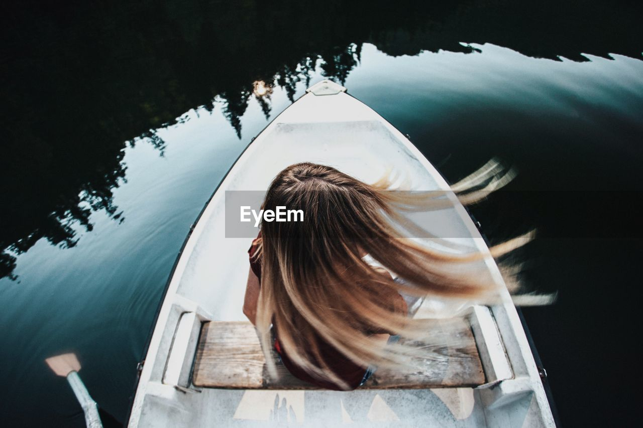 Rear View Of Woman Tossing Hair While Sitting On Boat In Lake
