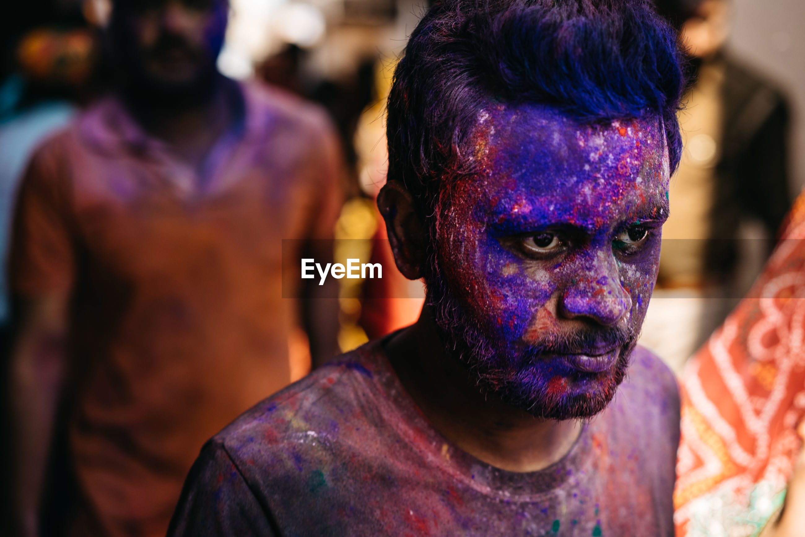 PORTRAIT OF MAN WITH MULTI COLORED FACE IN BACKGROUND