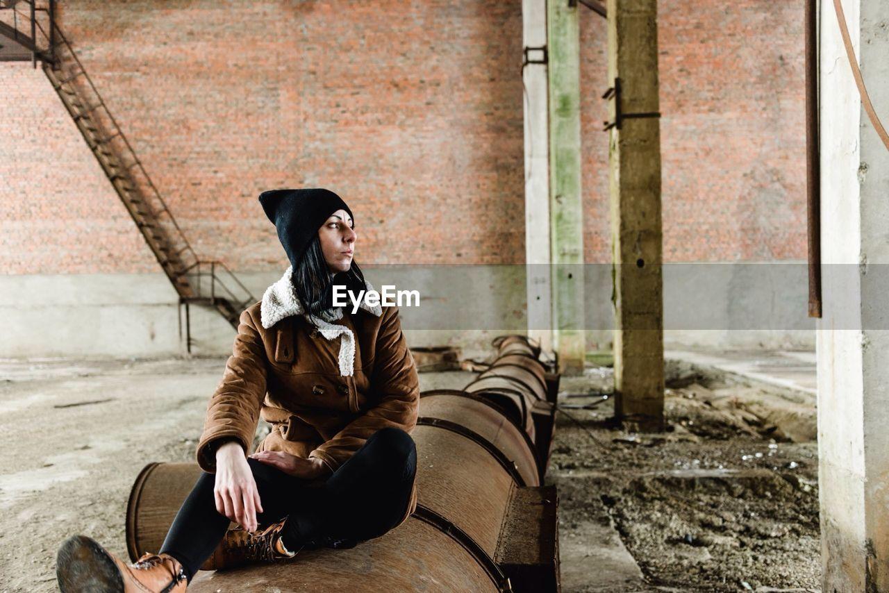 Full Length Of Woman Sitting On Barrel