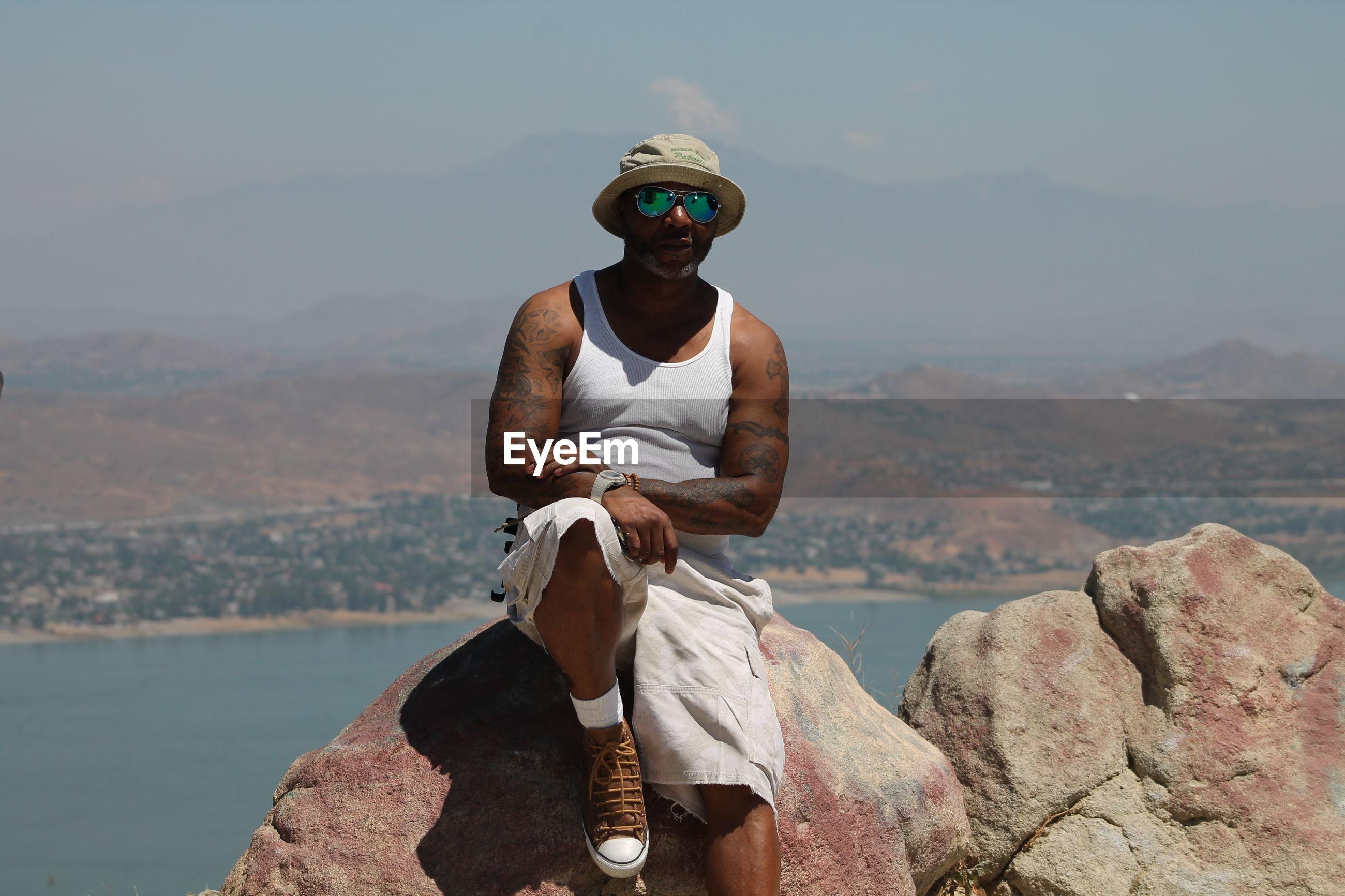 Portrait of man sitting on rock against lake