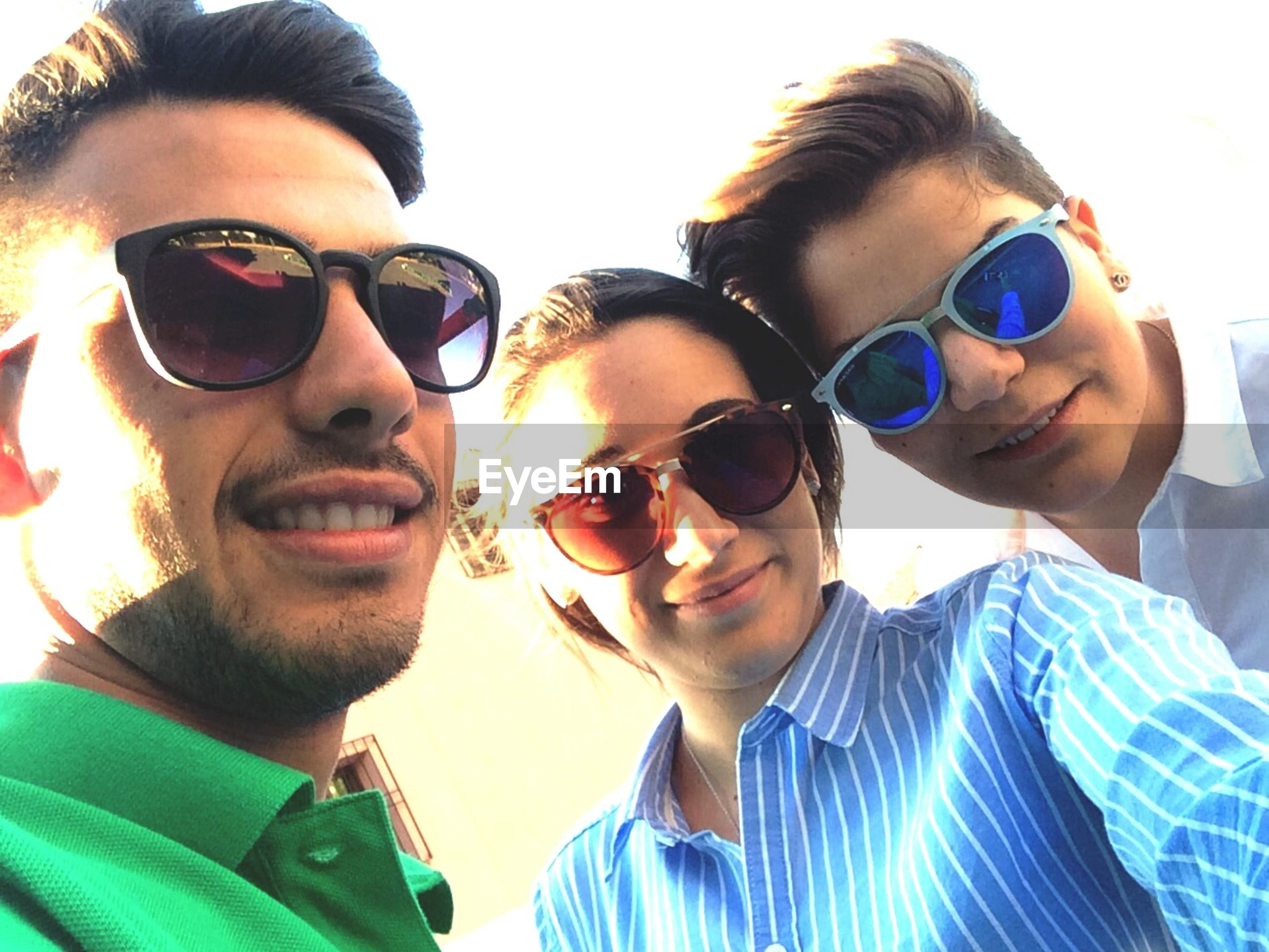 looking at camera, portrait, young adult, person, lifestyles, front view, leisure activity, smiling, young men, happiness, sunglasses, togetherness, casual clothing, bonding, toothy smile, headshot