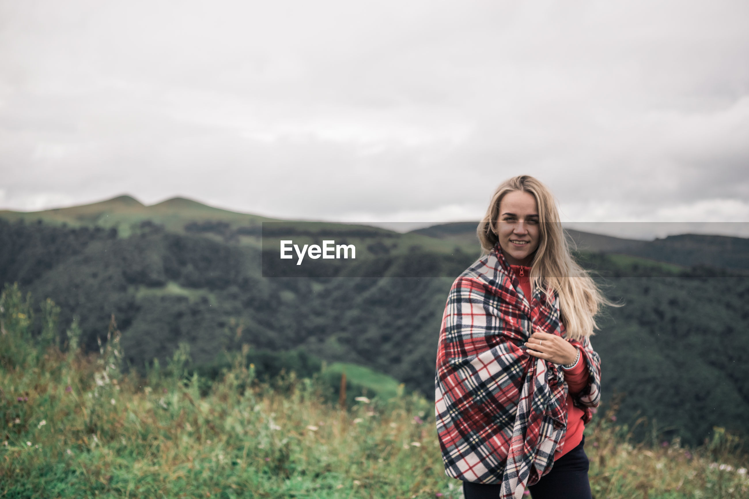 Portrait of smiling woman with blanket standing on mountain against sky
