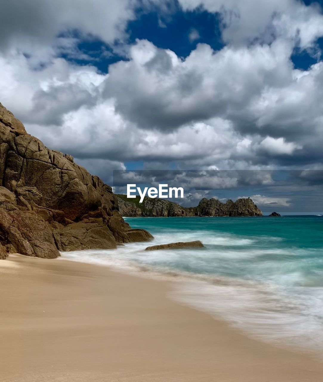 cloud - sky, land, sky, beach, water, sea, beauty in nature, scenics - nature, nature, rock, tranquility, day, rock - object, motion, sand, tranquil scene, solid, no people, rock formation, outdoors