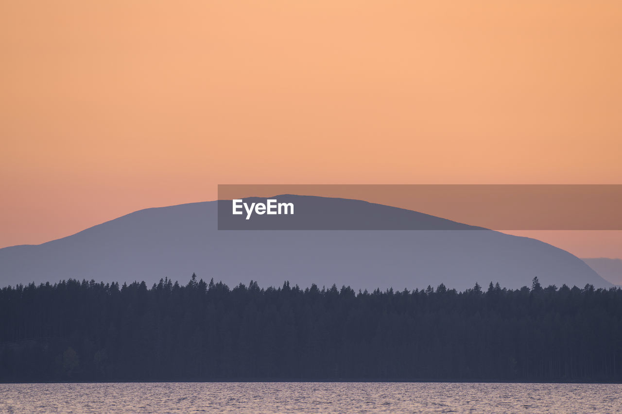 SILHOUETTE MOUNTAINS AGAINST CLEAR SKY DURING SUNSET