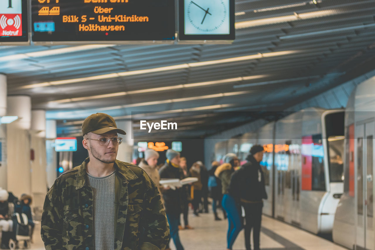 Man In Camouflage Jacket Standing At Railroad Station