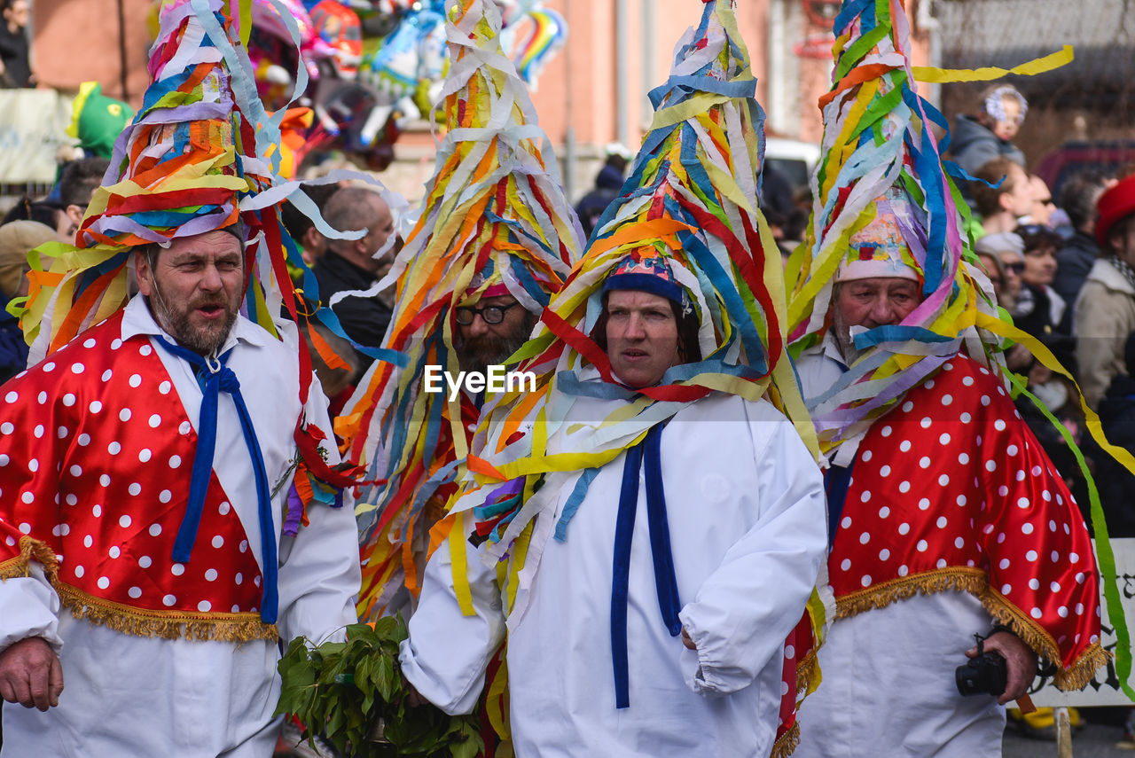 traditional clothing, cultures, multi colored, celebration, tradition, real people, day, traditional festival, event, lifestyles, front view, men, leisure activity, outdoors, togetherness, performance, happiness, young adult, people