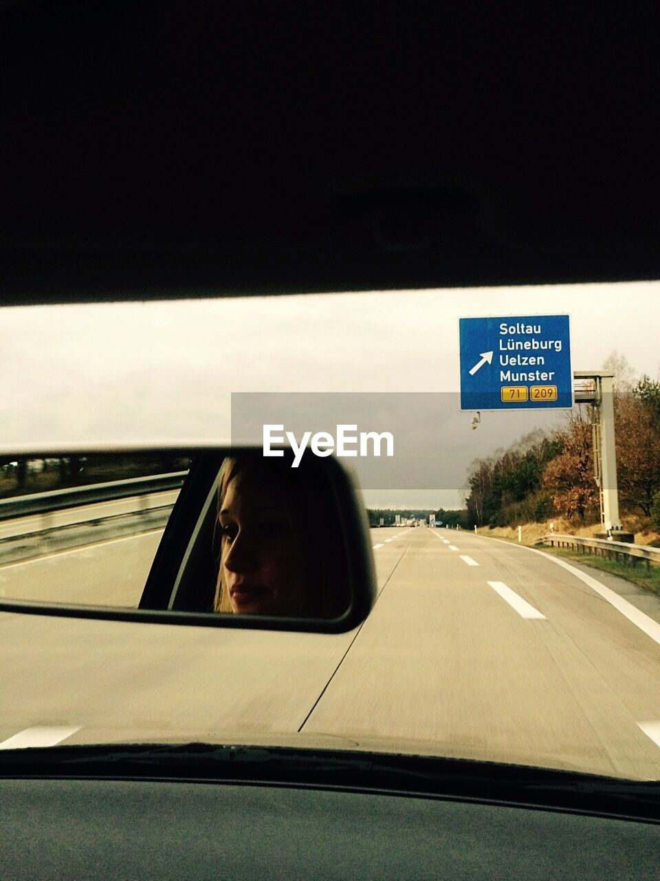 Woman Reflection In Rear-View Mirror In Car On Highway