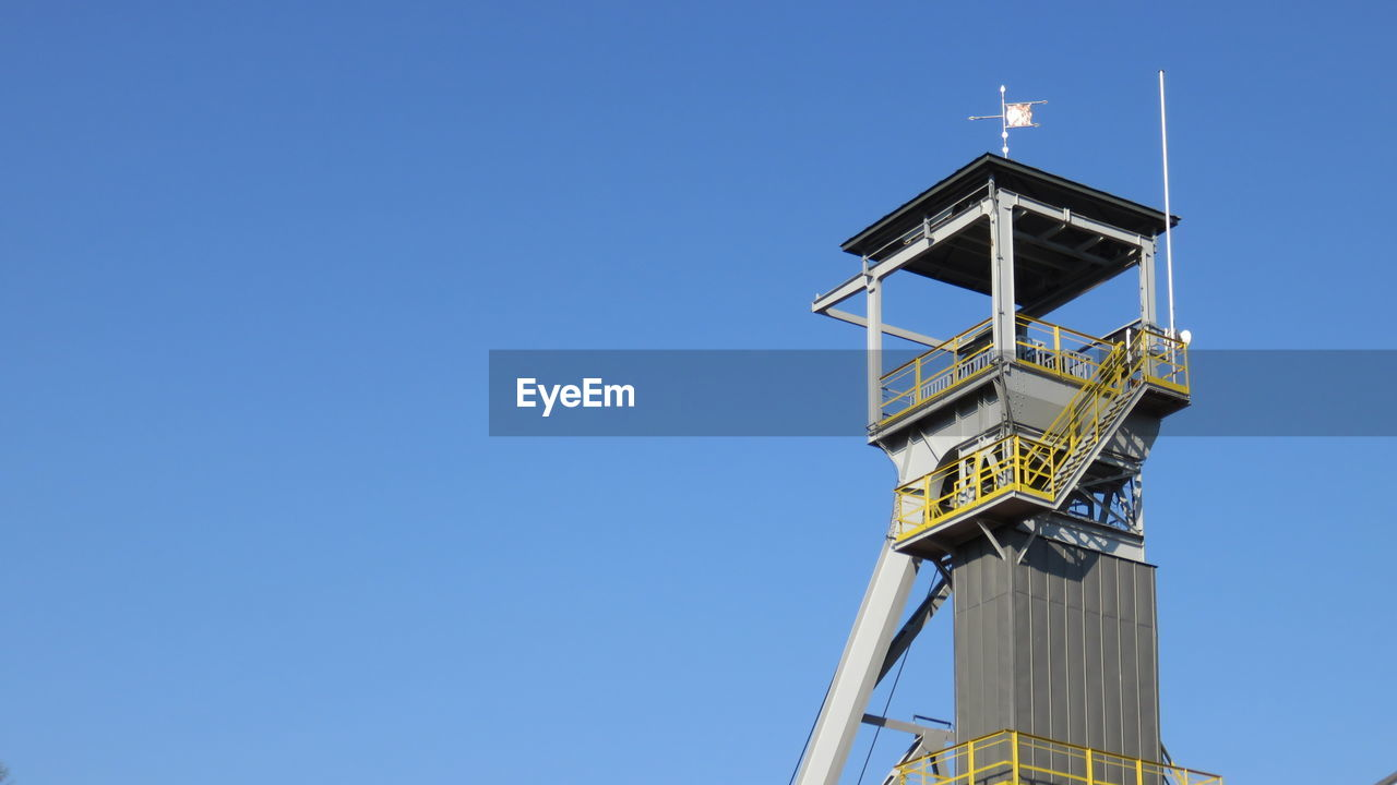 Low angle view of headframe at wieliczka salt mine against clear blue sky