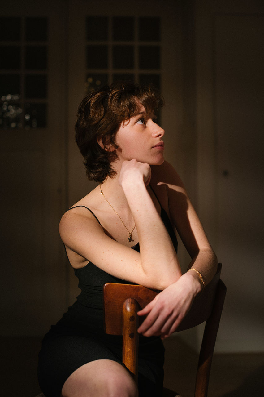 Thoughtful young woman looking away while sitting on chair at home