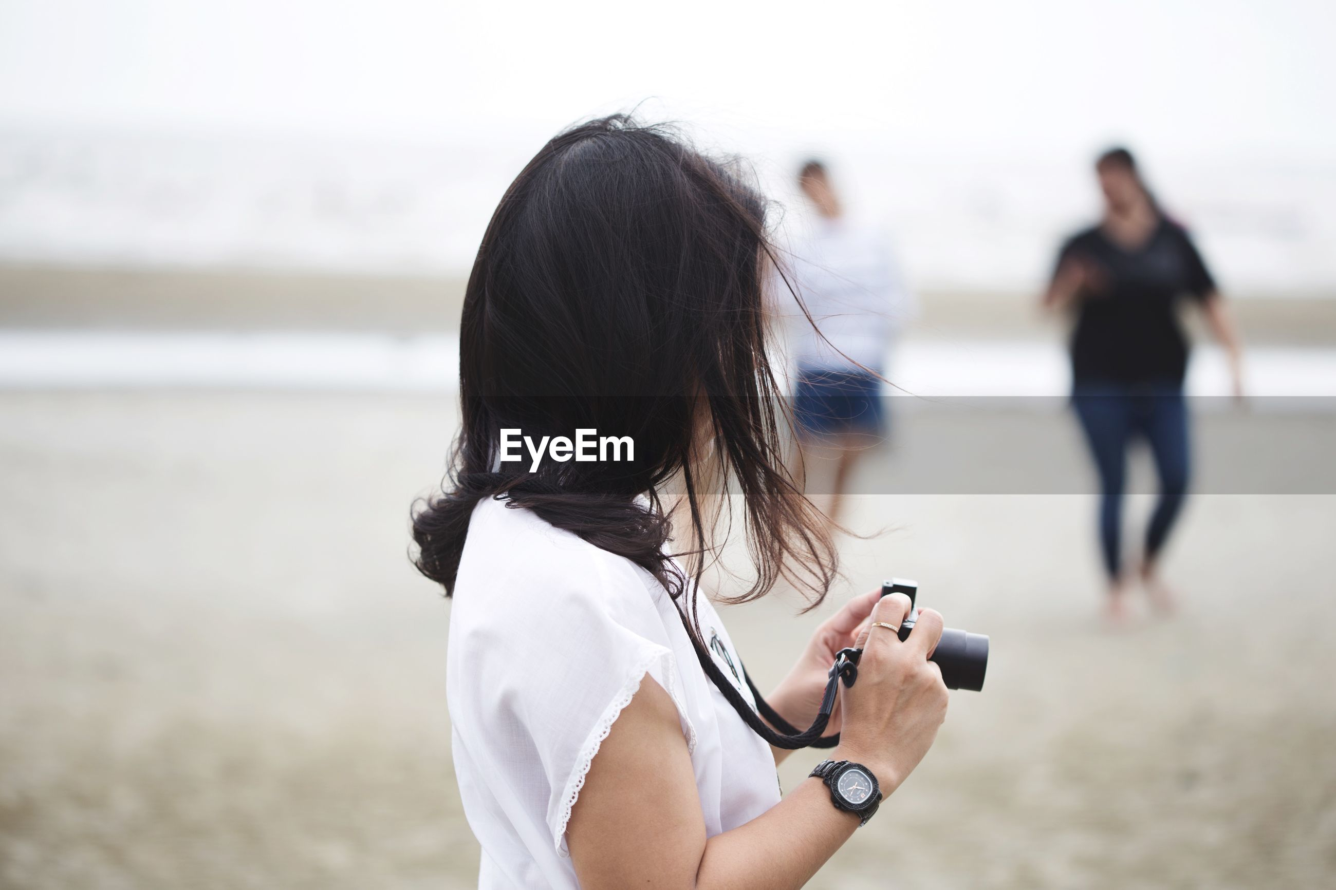 Side view of woman holding camera while standing at beach