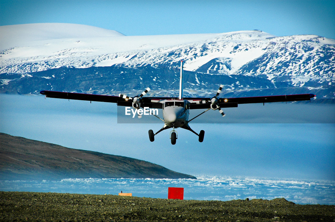 Biplane Flying Over Lake Against Snowcapped Mountains During Sunny Day