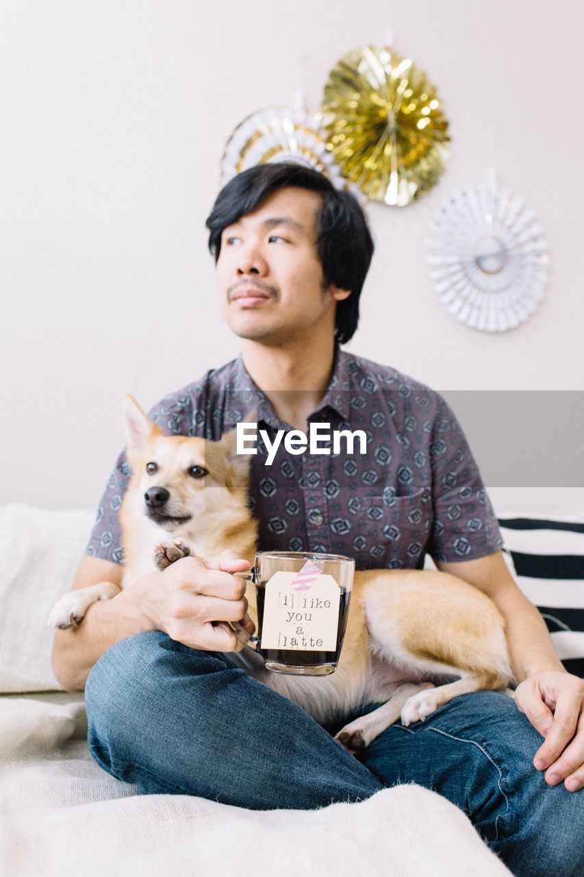 Thoughtful Man With Dog Holding Drink At Home