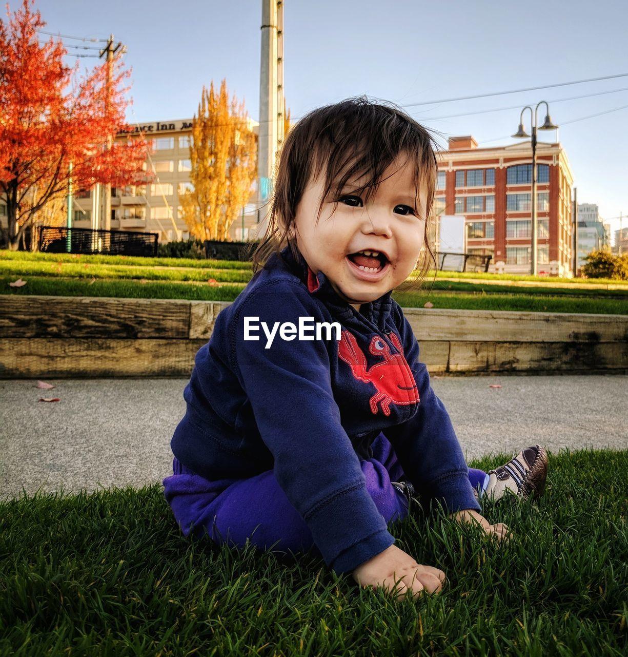 PORTRAIT OF CUTE SMILING BOY SITTING ON GRASS