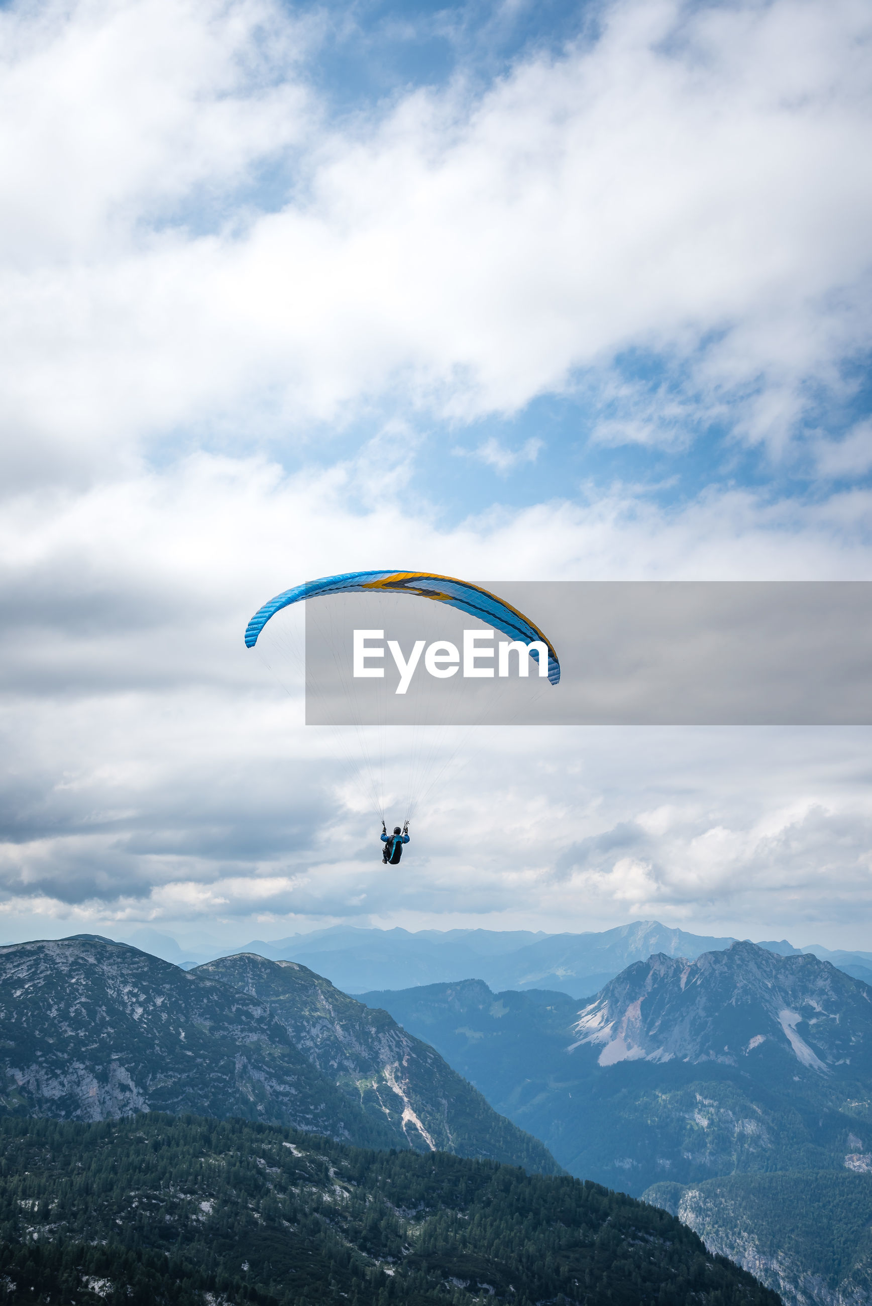 LOW ANGLE VIEW OF MAN PARAGLIDING AGAINST MOUNTAIN