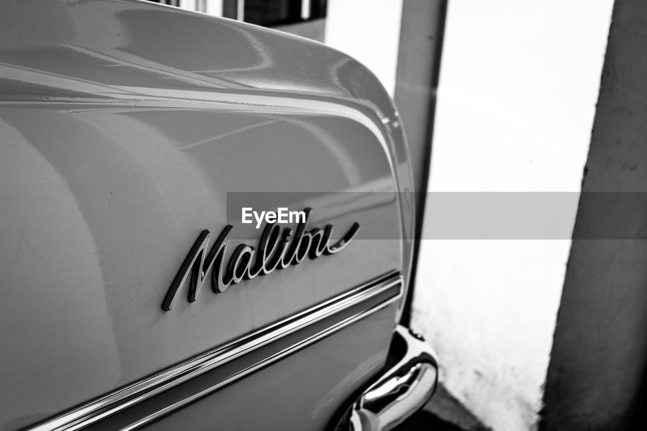 car, text, mode of transportation, land vehicle, motor vehicle, western script, transportation, communication, close-up, no people, vintage car, day, sign, metal, outdoors, vehicle part, retro styled, stationary, capital letter, luxury