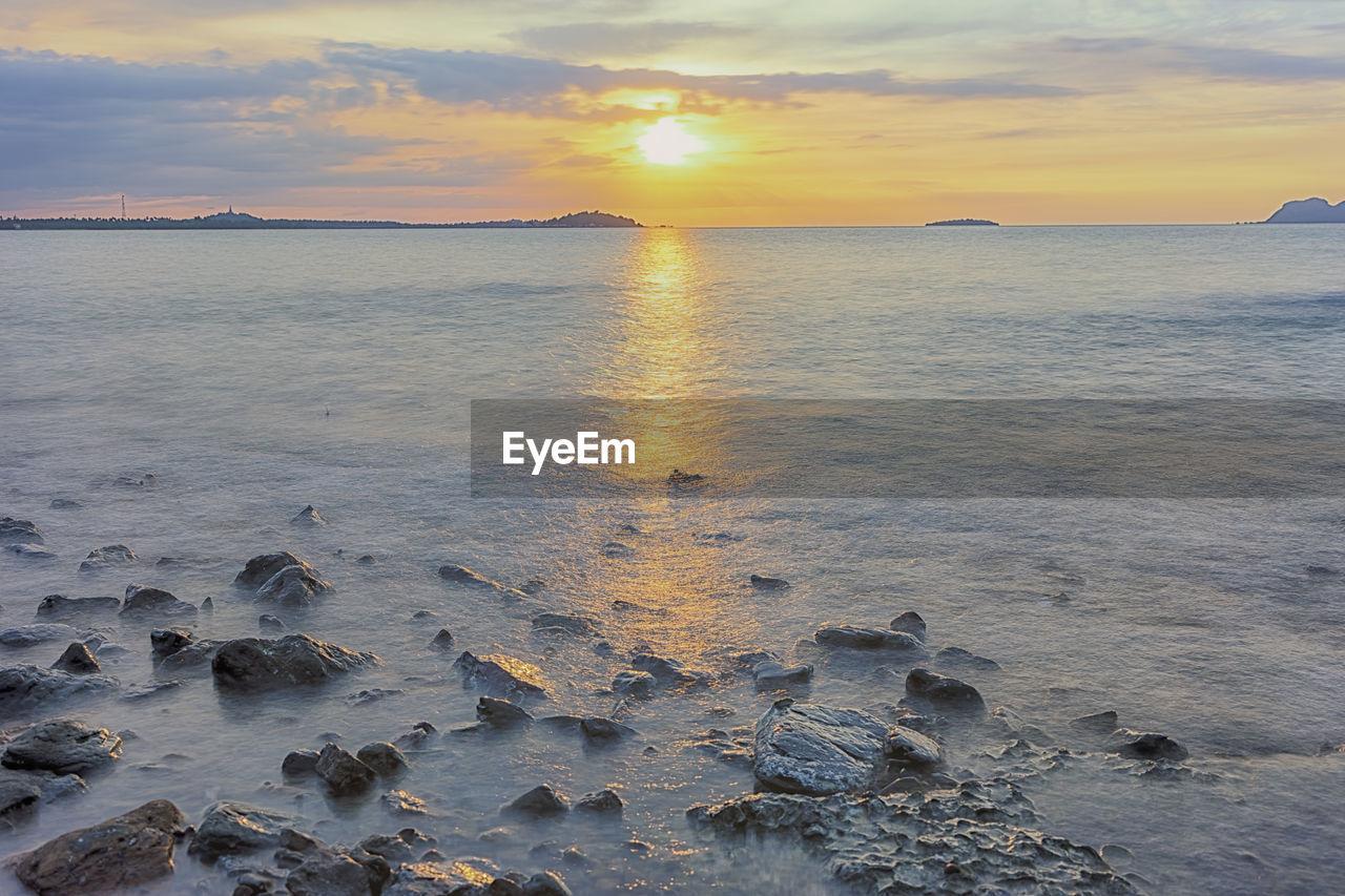 sky, sunset, water, scenics - nature, beauty in nature, sea, tranquility, tranquil scene, land, beach, nature, idyllic, cloud - sky, orange color, non-urban scene, sun, rock, horizon over water, no people