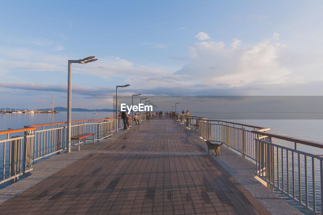 People On Bridge Over Seascape Against Cloudy Sky