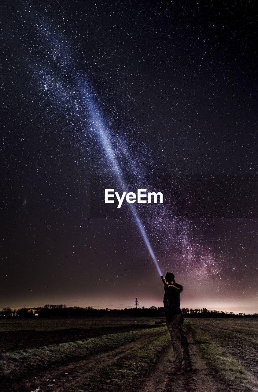 Mana With Flashlight Under Star Field At Night