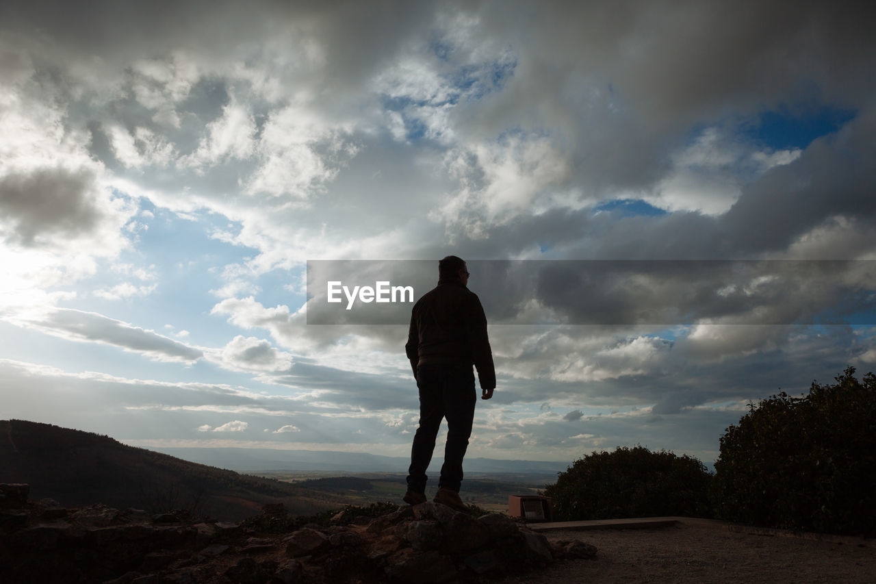 Rear view of man standing on rock at mountain against cloudy sky